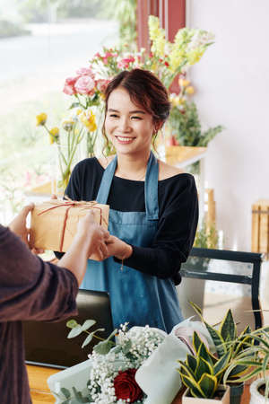 Cheerful pretty Vietnamese gift shop worker giving wrapped present to customer Archivio Fotografico - 132759877