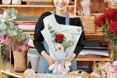 Cropped image of smiling young Vietnamese florist holding beautiful bouquet she made for customer Archivio Fotografico - 132669853
