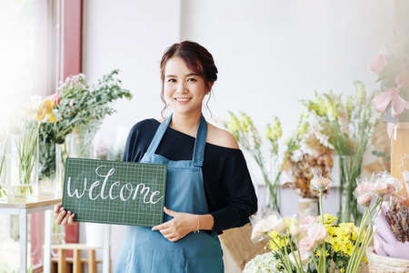 Pretty smiling young Vietnamese florist inviting customers to her new small flower shop Archivio Fotografico - 132759932