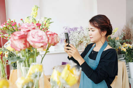 Young Vietnamese florist posing photos of finished bouquets on social media Archivio Fotografico - 132759934