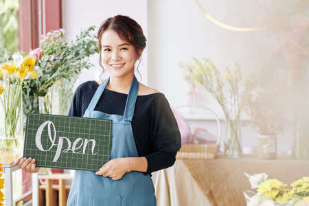 Pretty young female flower shop owner holding open sign and smiling at camera Archivio Fotografico - 132760045