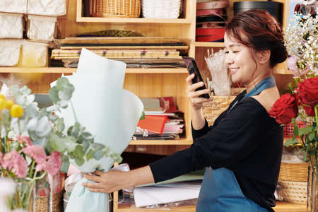 Young Asian woman taking photo of beautiful flower bouquet she made in her studio Archivio Fotografico - 132760048