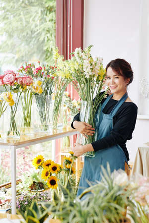 Cheerful young Asian florist standing among flowers with transparent glass vase Archivio Fotografico - 132760049