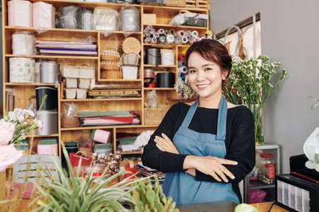 Portrait of young positive florist in blue apron standing at counter with her arms folded and smiling at camera Archivio Fotografico - 132760051