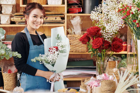 Portrait of pretty smiling florist with beautiful bouquet of flowers standing in her studio Archivio Fotografico - 132760054
