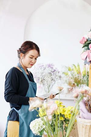 Young Asian flower shop owner ordering flowers online via application on tablet computer Archivio Fotografico - 132760058