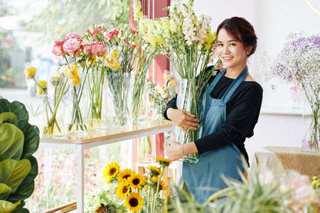 Smiling young Asian woman placing vases with various beautiful blooming flowers in flower boutique