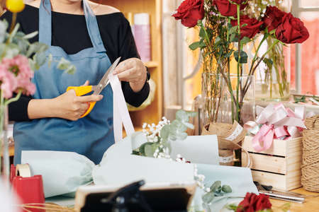Cropped image of florist cutting decorative ribbon when working on bouquet Archivio Fotografico - 132671872
