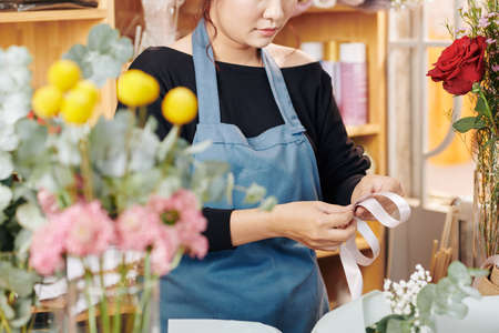 Cropped image of florist using light pink ribbon to make bow when wrapping presents and flowers Archivio Fotografico - 132671957