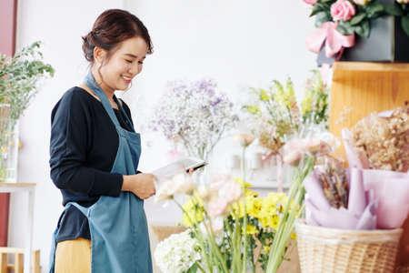 Hübsche lächelnde junge Floristin mit Tablet-Computer beim Überprüfen von Blumen in ihrem Geschäft Standard-Bild