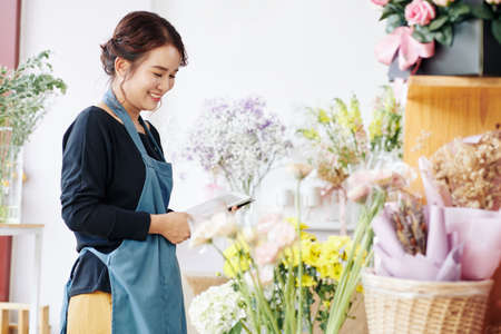 Pretty smiling young florist using tablet computer when checking flowers in her store Stock Photo