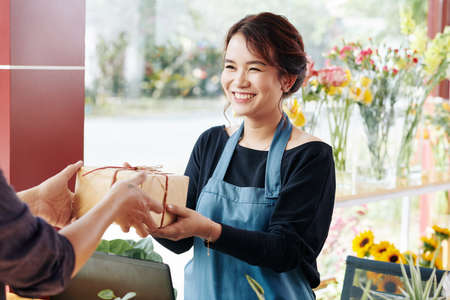 Cheerful young Asian florist giving gift box to client sho ordered it online