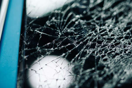 Close-up image of smartphone with screen covered with many cracks