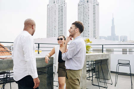 Positive colleagues talking and discussing news at rooftop party Stock Photo