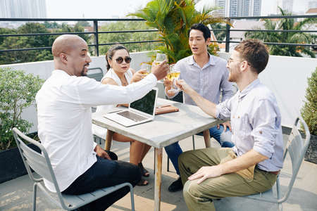 Business people sitting table on outdoor terrace and toasting with champagne glasses after successful meeting