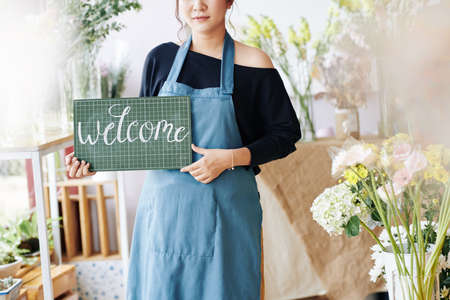 Cropped image of flower shop owner holding plastic signboard with chalk inscription and welcoming clients Archivio Fotografico - 132759494