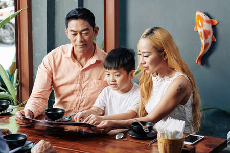 Vietnamese family of three sitting at cafe table, reading menu and choosing dishes to order