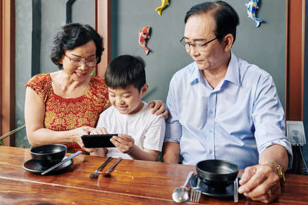 Happy Asian grandparents and grandchild sitting at cafe table and using mobile application on smartphone Stock Photo