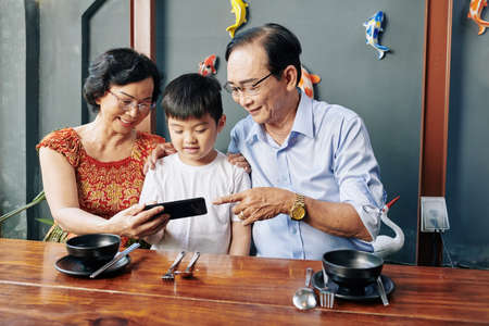 Senior Asian couple showing mobile application to grandson when they are sitting at cafe table