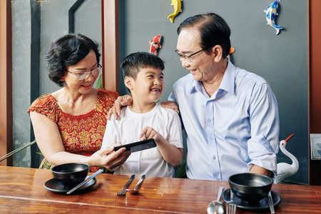 Happy Vietnamese boy showing game on smartphone screen to grandparents when they are sitting at cafe table Stock Photo