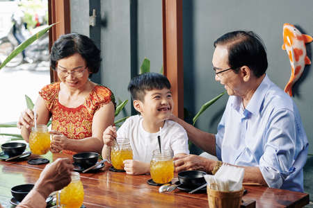 Happy little Vietnamese boy enjoying spending time with grandparents in cafe Stock Photo