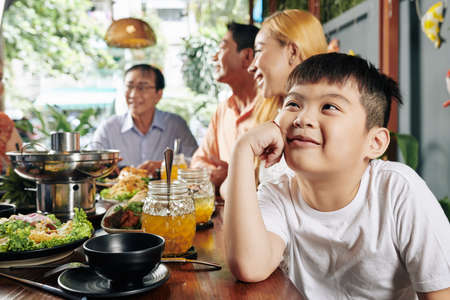 Adorable little Vietnamese boy smiling, looking up and dreaming when sitting at dinner table during family celebration Stock Photo