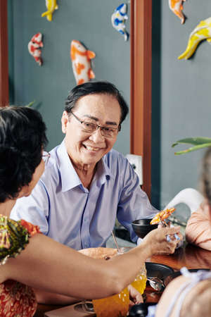 Smiling senior Vietnamese man giving bowl of soy sauce to his wife during family dinner in restaurant Stock Photo