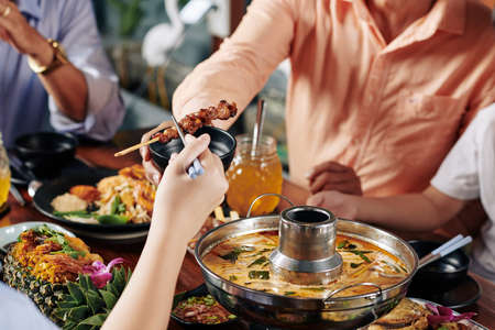 Hand of child taking delicious skewers with chopsticks when sitting at dinner table with relatives