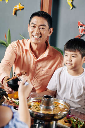 Smiling mature Vietnamese man having dinner with children and enjoying tasty Asian food