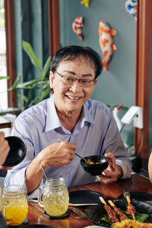Portrait of happy senior Vietnamese man in glasses eating tasty dish from small bowl at dinner table