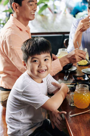 Portrait of cute smiling Asian boy sitting at dinner table with his family and looking at camera