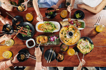 Big Asian family eating various tasty dishes and snacks with chopsticks at restaurant table, view from the top