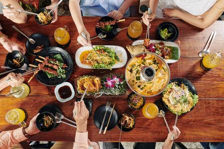 Gran familia asiática comiendo varios platos y bocadillos sabrosos con palillos en la mesa del restaurante, vista desde la parte superior