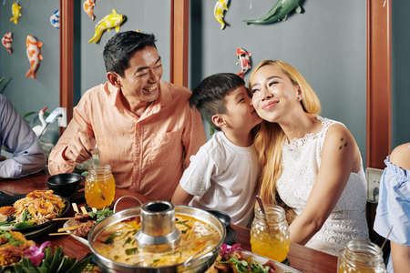 Happy cute little VIetnamese boy kissing his beautiful smiling mother on cheek when they are having family dinner in restaurant