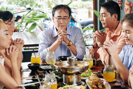Senior Vietnamese head of family closing eyes and praying at dinner table with relatives