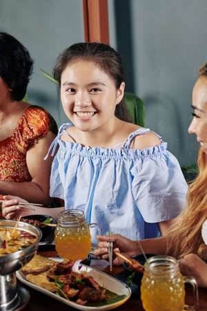 Portrait of lovely smiling Vietnamese girl eating dinner with chopsticks and looking at camera