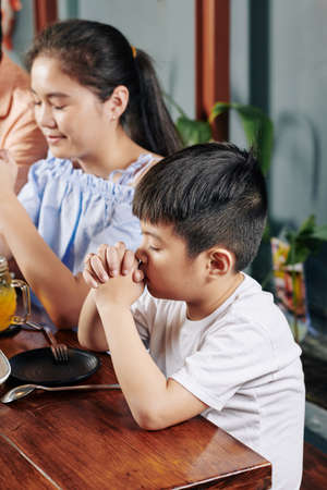 Adorable little Asian boy and his preteen sister praying before having meal at home