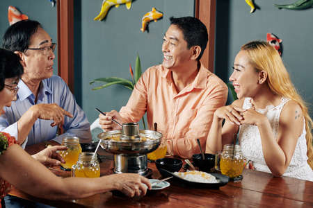 Cheerful mature couple and their senior parents talking and joking when having dinner at home together