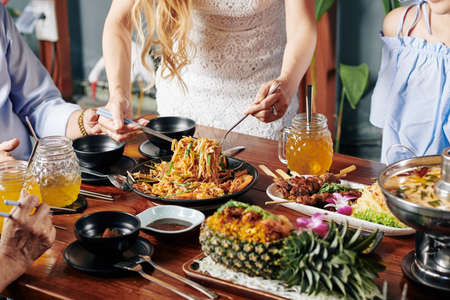 Cropped image of housewife serving food at dinner table with various delicious dishes of Asian cuisine Stock Photo