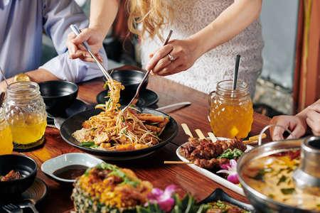 Hausfrau mischt Zutaten in leckerem asiatischem Gericht mit Sprossen, Garnelen und Soba am Esstisch