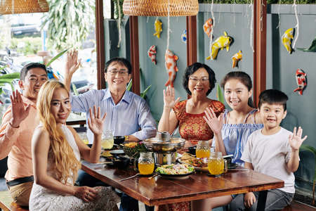 Happy big Vietnamese family sitting at dinner table with traditional Asian food, waving with hands and looking at camera Stock Photo