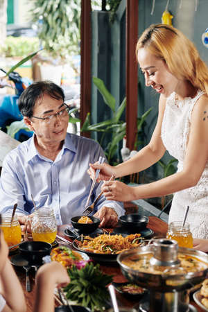 Lovely smiling housewife putting food from big dish to plate of her father-in-law at family dinner 스톡 콘텐츠