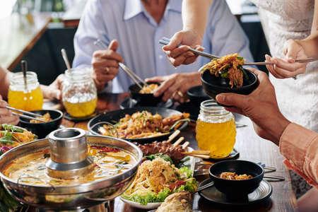 Ausgeschnittenes Bild von Menschen, die sich am Feiertagstisch versammelt haben, um köstliches asiatisches Essen mit leckeren süßen Getränken zu essen? Standard-Bild