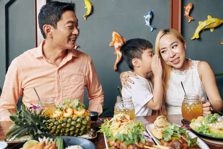 Adorable little Asian boy whispering secret to his mother during family dinner in cafe Stock Photo
