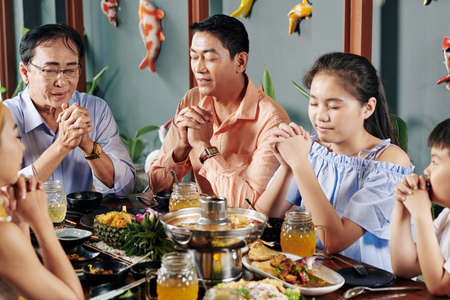 Vietnamese family members closing eyes when praying before having dinner at home Stock Photo