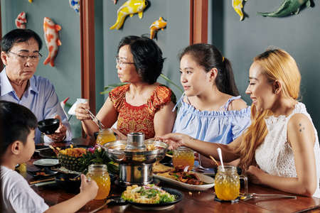Happy Vietnamese family eating traditional dishes and discussing news at dinner table in cafe
