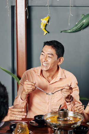 Portrait of happy middle-aged Vietnamese man eating noodles with spoon and chopsticks Stock Photo
