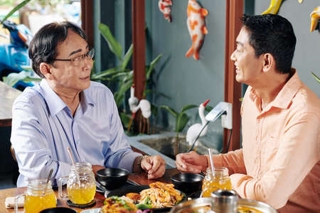 Smiling mature man talking to his father when eating delicious Asian food in restaurant