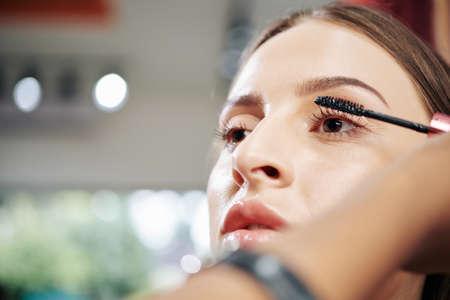 Attractive young Caucasian woman having voluminous mascara applied in beauty salon Stock fotó