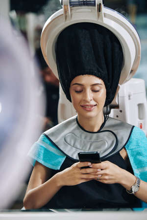 Smiling young woman texting friends and checking social media when receiving hair treatment in beauty salon